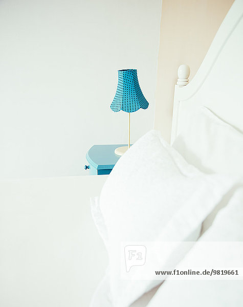 Indonesien, Bali, Tischlampe auf blauem Nachttisch und Bett im Schlafzimmer einer Ferienvilla