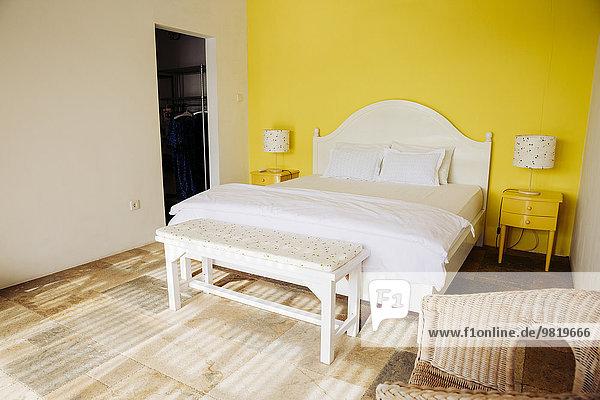Indonesien  Bali  Schlafzimmer mit gelber Wand und gelben Nachttischen einer Ferienvilla
