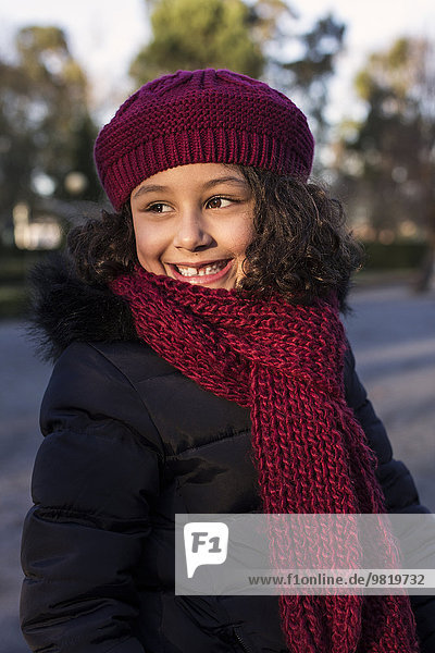 Portrait of smiling little girl wearing wool cap and scarf