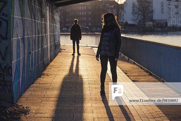 Deutschland  Berlin  Teenagerpaar unter einer Brücke bei Abendsonne