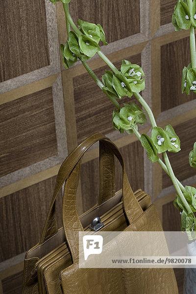 Altmodische braune Handtasche und Zweige von Bells of Ireland vor hölzerner Wandverkleidung