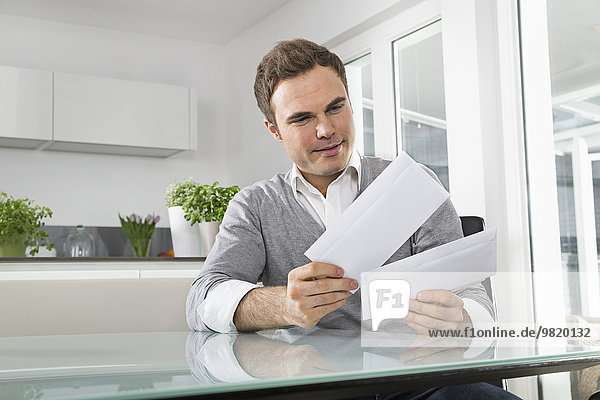 Man sitting in kitchen with letters
