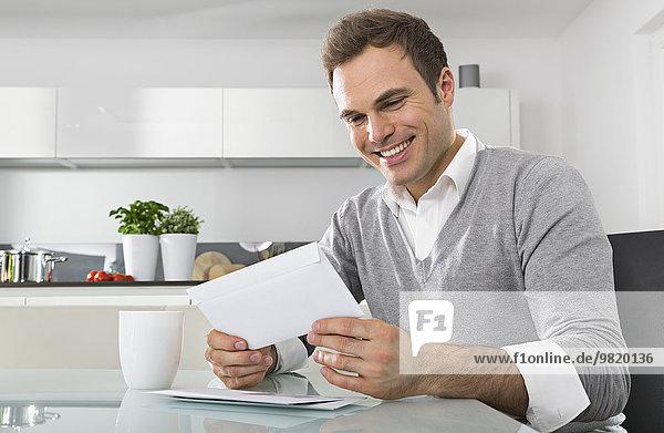Smiling man sitting in kitchen watching envelope