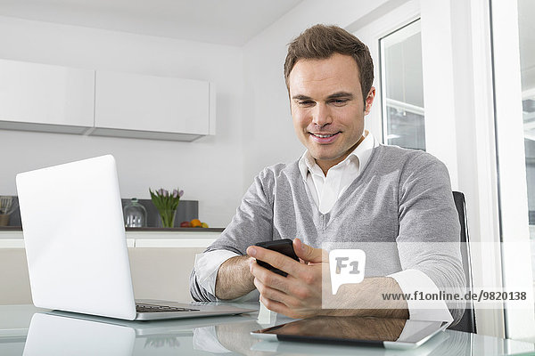 Lächelnder Mann sitzend in der Küche mit Laptop über Smartphone