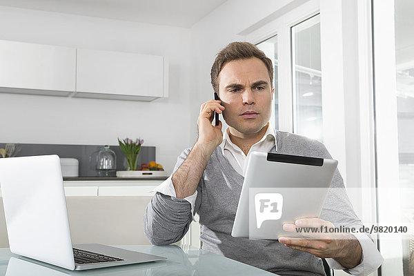 Mann sitzend in der Küche mit Laptop mit digitalem Tablett und Smartphone