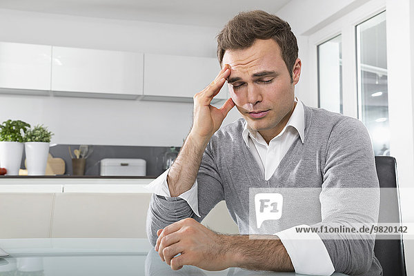 Man with closed eyes sitting in kitchen with hand on his face
