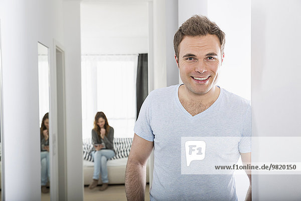 Portrait of smiling man standing in corridor while woman waiting in the background