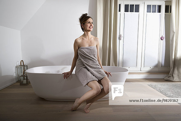 Smiling woman sitting on the edge of modern bathtub drinking champagne