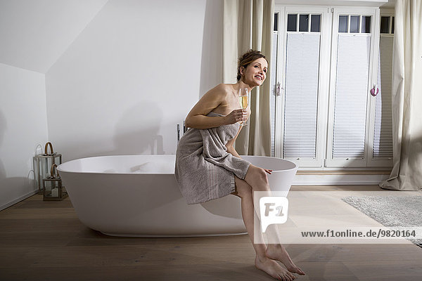 Woman sitting on the edge of modern bathtub with glass of champagne
