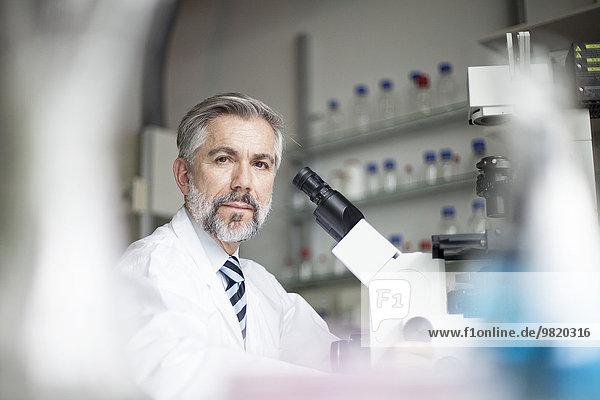 Porträt eines Wissenschaftlers im Labor mit Mikroskop