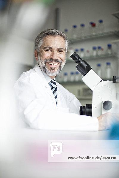 Porträt eines lächelnden Wissenschaftlers im Labor mit Mikroskop