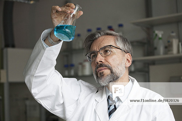 Wissenschaftler im Labor zur Untersuchung von Flüssigkeit in Erlenmeyerkolben