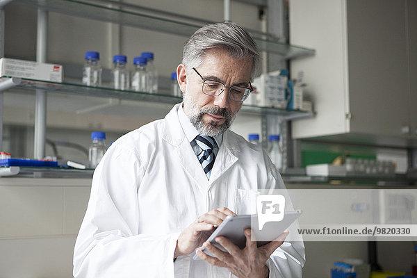 Wissenschaftler mit digitalem Tablett im Labor