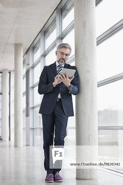 Geschäftsmann  der sich mit Hilfe eines digitalen Tabletts gegen die Säule lehnt