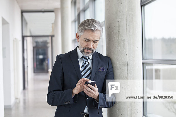 Businessman leaning against column using smartphone