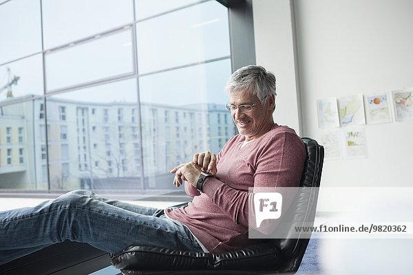 Mann sitzt in einem Ledersessel mit smartwatch