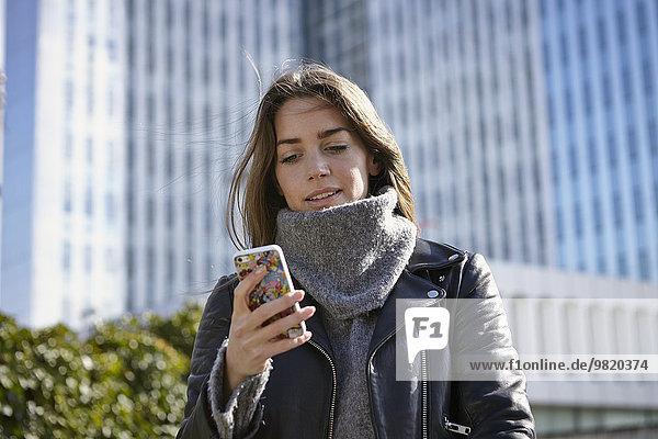 Deutschland  Düsseldorf  Junge Frau mit Smartphone