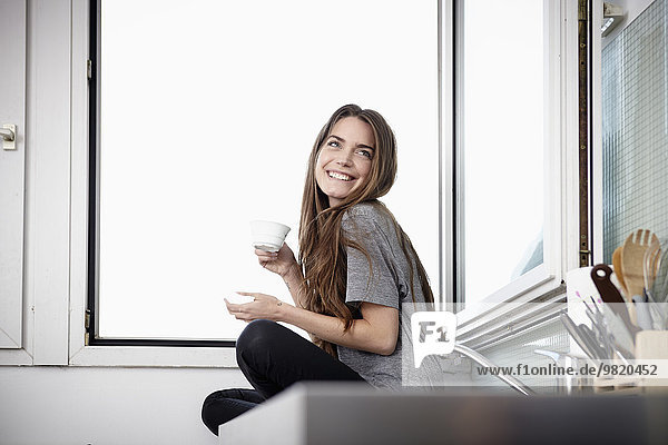 Young woman in kitchen sitting at window drinking coffee