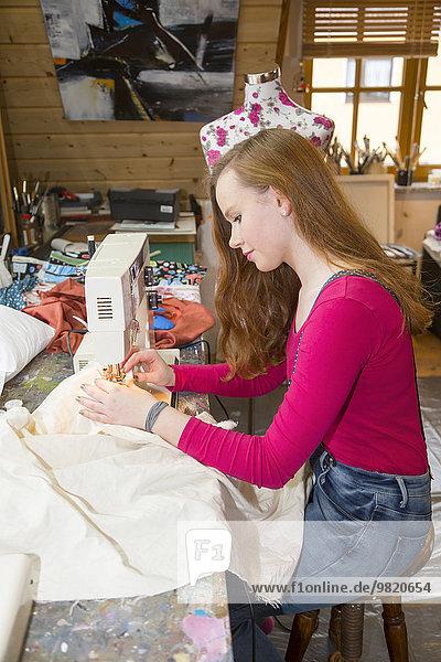 Teenagerin mit Nähmaschine in der Werkstatt