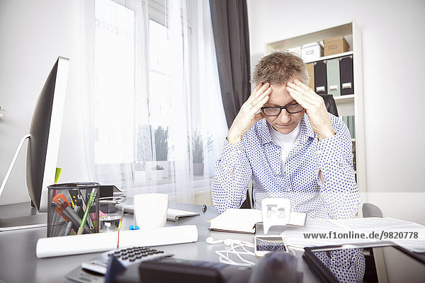 Overstressed businessman at his desk at home office