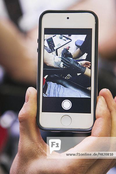 Man's Hand hält Smartphone mit Fotografie von Tattoo-Künstler bei der Arbeit