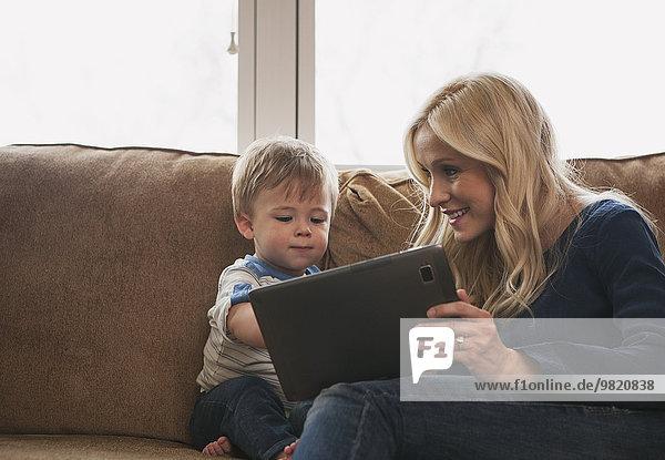 Mutter und kleiner Sohn sitzen auf der Couch und benutzen gemeinsam ein digitales Tablett.