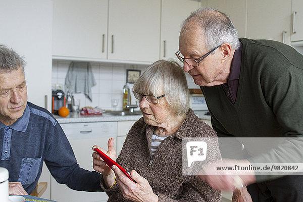 Senioren einer Wohngemeinschaft mit digitalem Tablett