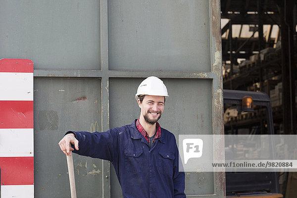 Lächelnder Arbeiter vor der Fabrikhalle