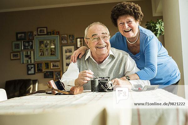 Glückliches Seniorenpaar mit alter Kamera zu Hause