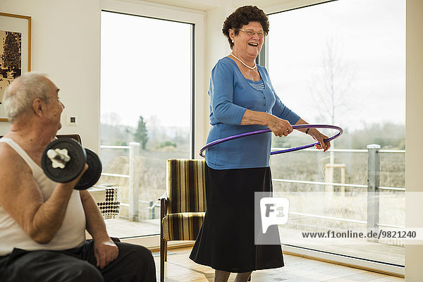 Senior man with dumbbell and his wife with hula-hoop at home