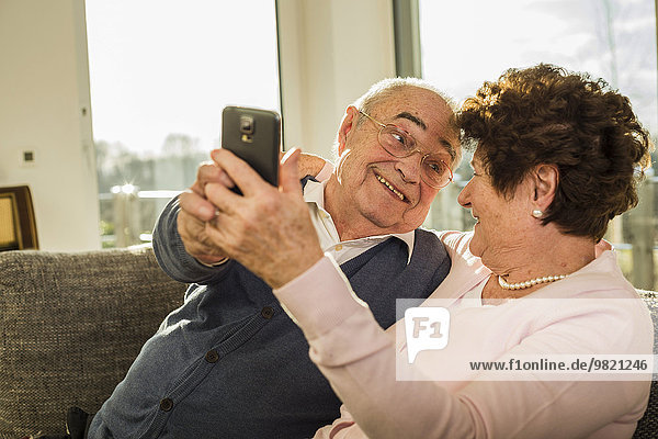 Senior couple taking a selfie with smartphone at home