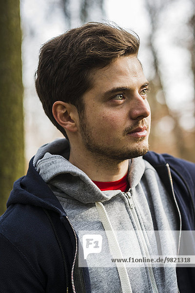 Young man wearing hooded jacket outdoors