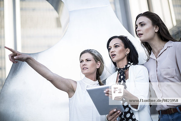 Three women with digital tablet in the city