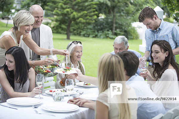 Frau beim Auftischen von Salat auf einer Gartenparty