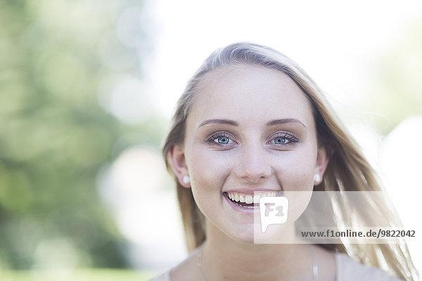 Porträt einer lächelnden blonden jungen Frau im Freien