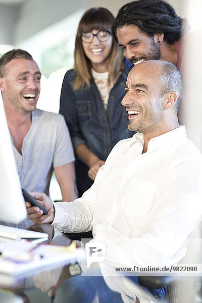 Man showing co-workers something on his phone
