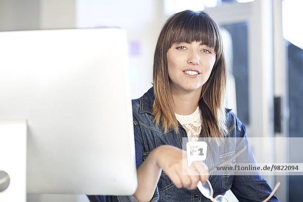 Porträt einer jungen Frau am Schreibtisch im Büro