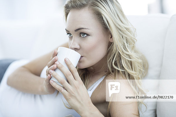 Blond woman lying on a couch drinking coffee