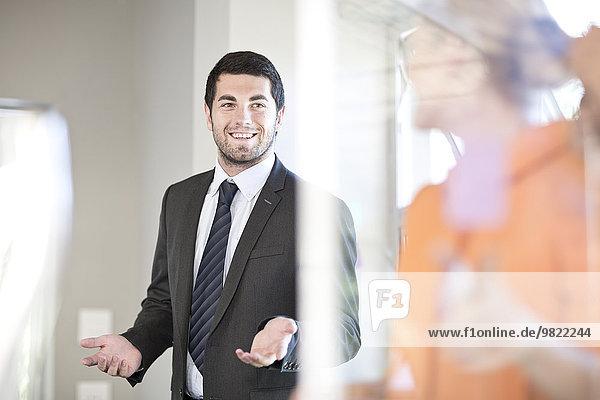 Zwei kommunizierende Geschäftsleute in einem Büro