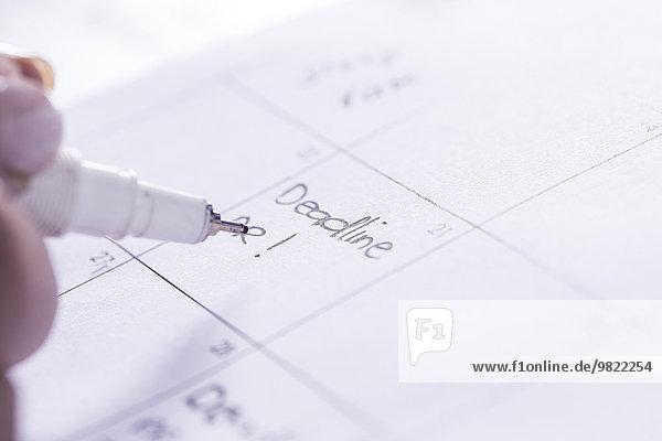 Frau notiert Datum im Tagesplaner