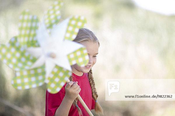 Südafrika  Mädchen auf Exkursion spielend mit Papierwindrad