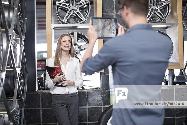 Mann fotografiert Frau in einem Reifengeschäft mit digitalem Tablett
