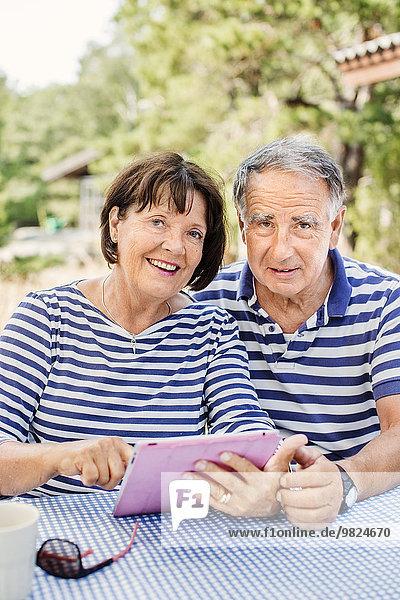 Mature couple using digital tablet