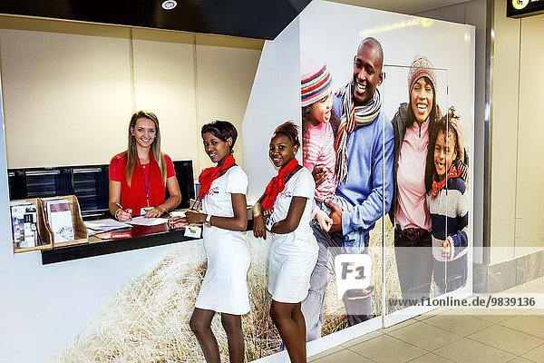 South Africa  African  Johannesburg  JNB  O. R. Tambo International Airport  terminal  Virgin Mobile  desk  customer service  Black  woman  coworkers  employees  uniforms.