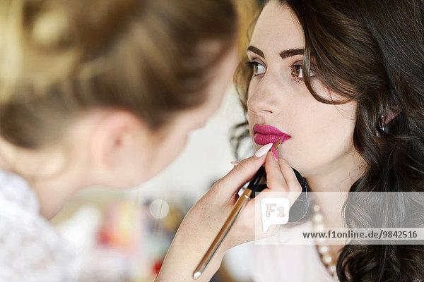 Junge Frau wird geschminkt von Visagistin