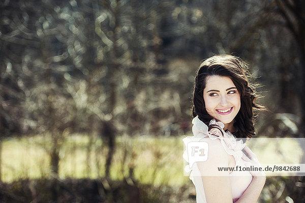 Portrait einer lachenden jungen Frau mit braunen Haaren