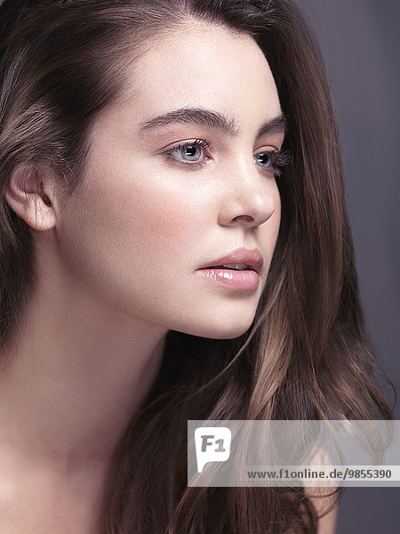 Beauty portrait of a young woman with grey eyes and long light brown hair  close-up of face