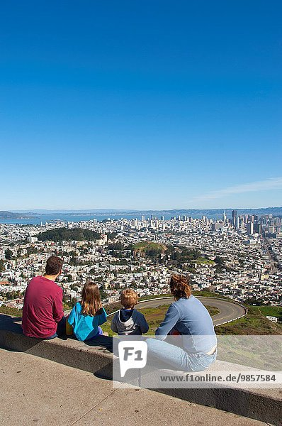 A family is looking at the downtown area of San Francisco  California  USA from the Twin Peaks.