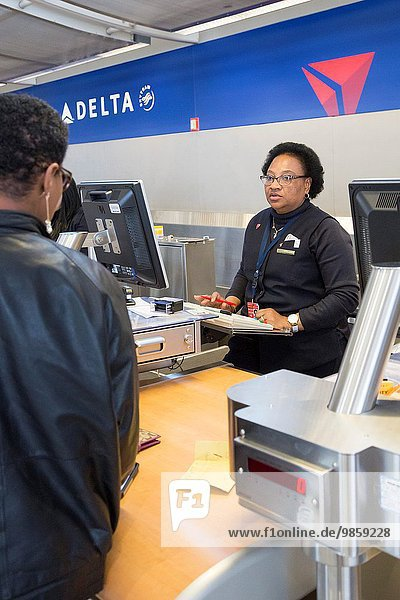 Romulus  Michigan - A Delta Air Lines ticket agent checks in a passenger at Detroit Metro Airport.