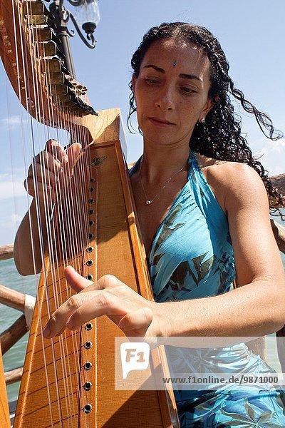 Women playing harp  Caribean Sea.